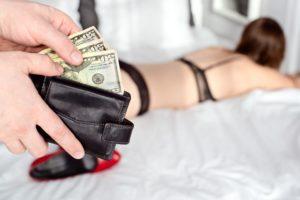 風俗嬢に料金を手渡す男性